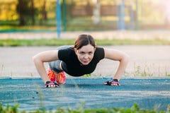 Сильная женщина нажимает вверх outdoors на парке стоковая фотография