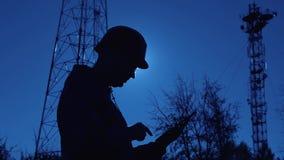 Силуэт инженера на заходе солнца, который смотрит штендеры радиосвязи Инженер пишет данные в планшет _ сток-видео