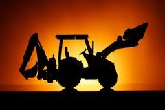 Силуэт трактора Backhoe, оранжевая предпосылка захода солнца стоковая фотография rf