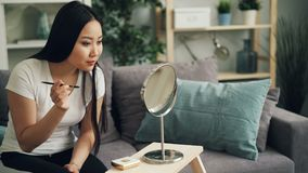 Симпатичная молодая женщина красит брови используя косметики и щетку после этого смотря в зеркале и усмехаться Девушка сток-видео
