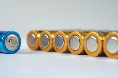 Сине-золотой конец-вверх батарей AA на белой предпосылке Малая глубина поля, макроса стоковое изображение