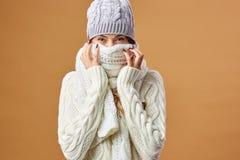 Славная девушка одетая в белых связанных свитере и шляпе закрывает ее сторону с белым шарфом на бежевой предпосылке в студии стоковое фото