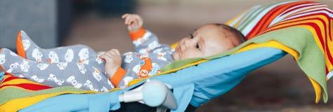 славный голубой наблюданный ребенок младенца ослабляя на sunbed или покрашенный шезлонгом знамени хвастуна дома длинный стоковые изображения