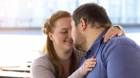 Сладостные пары в влюбленности нюхая сидеть на стенде города, выходные совместно, сомкнутость стоковая фотография