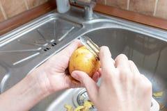 Слезающ картошки в домашней кухне - непознаваемый человек держа нож и слезть картошки в конце кухонной раковины вверх - стоковые изображения