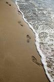 След ноги на песке с морем, вертикальный формат стоковые фотографии rf