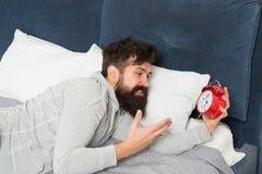 Слишком раньше бородатый будильник ненависти человека пока лежащ в кровати дома Человек с будильником Бодрствование утра вверх Со стоковое фото
