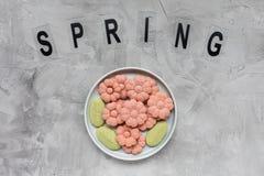 Слово ВЕСНЫ и печенья цветка на плите на серой предпосылке Праздники весны варя концепцию стоковое фото