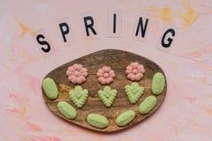 Слово ВЕСНЫ и печенья цветка на деревянной доске на розовой предпосылке Праздники весны варя концепцию стоковое изображение