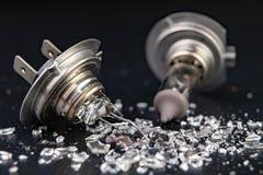 Сломленный шарик для фары автомобиля Разлитое стекло и сломленная нить на таблице мастерской стоковая фотография rf