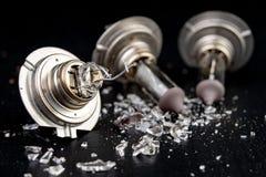 Сломленный шарик для фары автомобиля Разлитое стекло и сломленная нить на таблице мастерской стоковые изображения rf