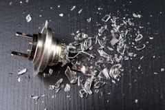 Сломленный шарик для фары автомобиля Разлитое стекло и сломленная нить на таблице мастерской стоковые изображения
