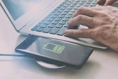 Смартфон поручая на беспроводном заряжателе стоковые изображения rf