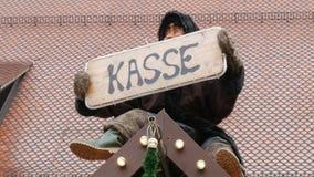 Смешная двигая кукла сидит на стойке рождества и держит в его руке знак который говорит кассир на немецком акции видеоматериалы