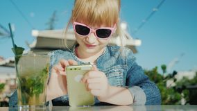 Смешная девушка в розовых играх стекел на смартфоне Сидит на квартире лета в кафе акции видеоматериалы