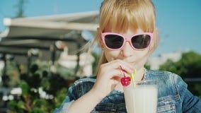 Смешная девушка в розовых стеклах выпивает коктейль на летней террасе кафа Остатки с концепцией детей акции видеоматериалы