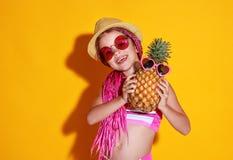 Смешная счастливая девушка ребенка в купальнике, розовых стеклах и шляпе с ананасом смеется на желтой предпосылке стоковые фотографии rf