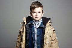 Смешной мальчик нес все его одежды стоковая фотография