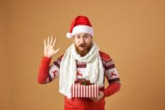 Смешной рыжеволосый человек с бородой одетой в красном и белом свитере с оленями, белом связанном шарфе и шляпе Санта стоковое изображение rf