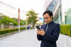Смущенный азиатский бизнесмен используя телефон в городе outdoors стоковые изображения rf