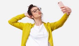 Снятый довольно молодой европейской женщины в случайных одеждах отправляя поцелуй воздуха в его парня пока стоящ и принимающ self стоковое изображение