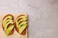 Сэндвич с авокадоом на темном хлебе рож сделал со свежим отрезанным авокадоом стоковое изображение rf