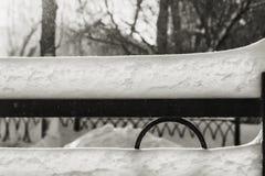 Сугроб белого снега с солнечностью и светом bokeh на черным загородке выкованной металлом на запачканной предпосылке в парке в зи стоковое фото