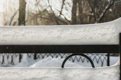 Сугроб белого снега с солнечностью и светом bokeh на черным загородке выкованной металлом на запачканной предпосылке в парке в зи стоковая фотография rf