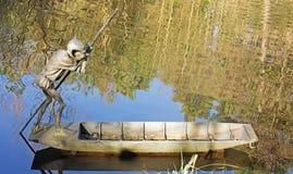 Статуя гоблина бить с рук на озере стоковая фотография rf