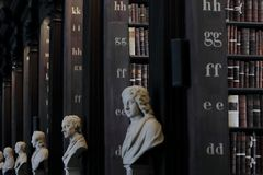Старая библиотека с историческими книгами и скульптурами стоковые изображения rf