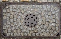 Старая крышка люка металла на улице булыжника, Польше стоковое фото