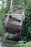 Старая детская дорожная коляска в саде стоковые фотографии rf