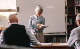 Старшие люди сидя в классе уча стоковая фотография rf