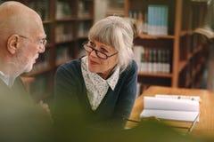 Старшие пары взаимодействуя друг с другом сидящ в библиотеке стоковое фото rf