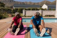 Старшие пары выполняя протягивающ тренировку в задворк дома стоковые фото