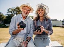 Старшие пары сидя в парке держа boules стоковое изображение
