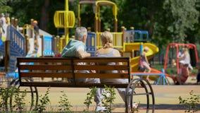 Старшие пары сидя на стенде около спортивной площадки, наблюдая играть внуков стоковое изображение rf