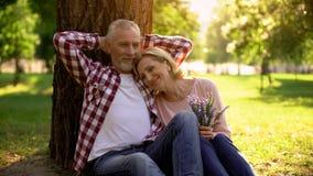 Старшие пары ослабляя на траве в парке и наслаждаясь романтичной датой, истинной любовью стоковые изображения rf