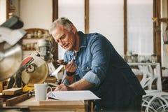 Старший плотник работая на его мастерской стоковая фотография