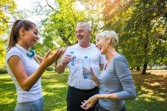 Старший человек и женщина и молодая женская разминка инструктора на свежем воздухе, их остатки и воде напитка стоковые изображения rf