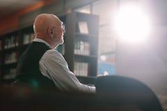Старший человек сидя в классе стоковое фото