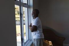 Старший человек смотря через окно дома стоковое фото