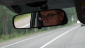 Старший человек управляет автомобилем на проселочной дороге Отражение стороны в зеркале заднего вида автомобиля closeup 4K сток-видео