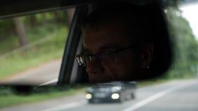 Старший человек управляет автомобилем на проселочной дороге Отражение стороны в зеркале заднего вида автомобиля closeup сток-видео