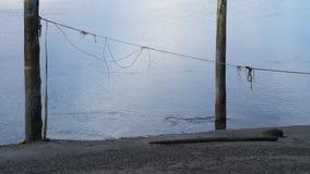 Старые деревянные штендеры пристани с веревочкой во время отлива стоковые фото