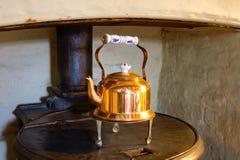 Старый английский медный чайник на печи стоковое фото