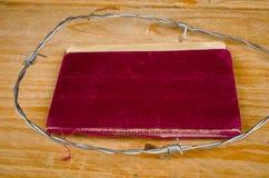 Старый паспорт окруженный колючей проволокой стоковая фотография rf