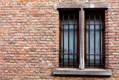 Старый дом с космосом экземпляра на стене красных кирпичей Старые деревянные окна с металлическими стержнями на старом доме кирпи стоковая фотография