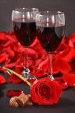 2 стекла вина, розы, лепестков и шоколадов на черной предпосылке стоковые изображения rf