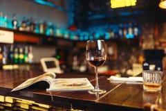 Стекло красного вина на деревянном счетчике бара, никто стоковое изображение